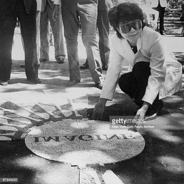 Yoko Ono examines the mosaic of the reversed Imagine at Strawberry Fields in Central Park