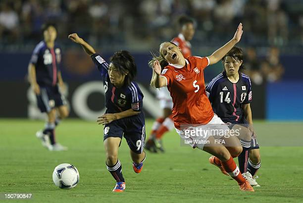 Yoko Tanaka of Japan competes for the ball with Anja Thuerig of Switzerland during the FIFA U20 Women's World Cup Japan 2012 Group A match between...