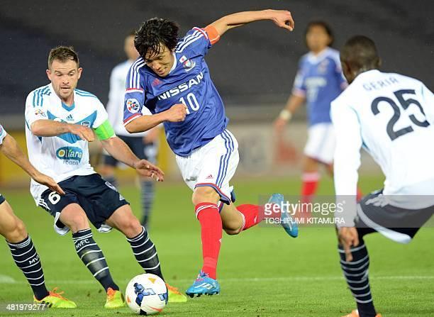 Yokohama F Marinos midfielder Shunsuke Nakamura dribbles the ball between Melbourne Victory midfielder Leigh Broxham and defender Jason Geria during...