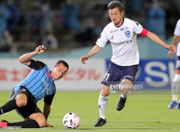 Yokohama FC forward Kazuyoshi Miura is tackled by Kawasaki Frontale forward Leandro Damiao during the JLeague football match between Kawasaki...
