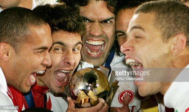 Brazil's SC Internacional players share the joy as they hold the winner's trophy during the awards ceremony after their 10 victory against FC...