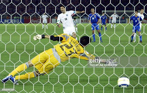 Iranian footballer and captain Ali Daei scores a penalty as Japanese goalkeeper Yoshikatsu Kawaguchi reaches for the ball during the second half of...