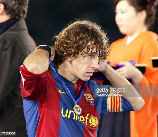 Spain's FC Barcelona football captain Carlos Puyol adjusts his silver medal after defeat by Brazil's Internacional in the final match of the FIFA...
