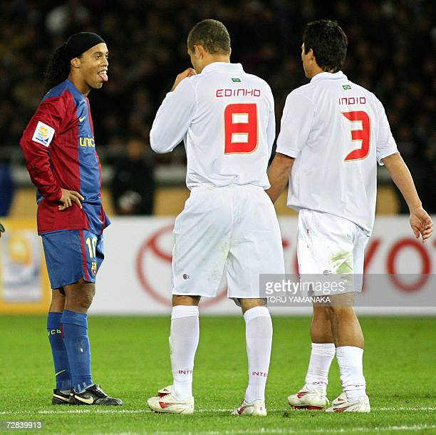 Spain's FC Barcelona forward Ronaldinho of Brazil puts out his tongue after missing a free kick as he stands beside Brazil's SC Internacional...