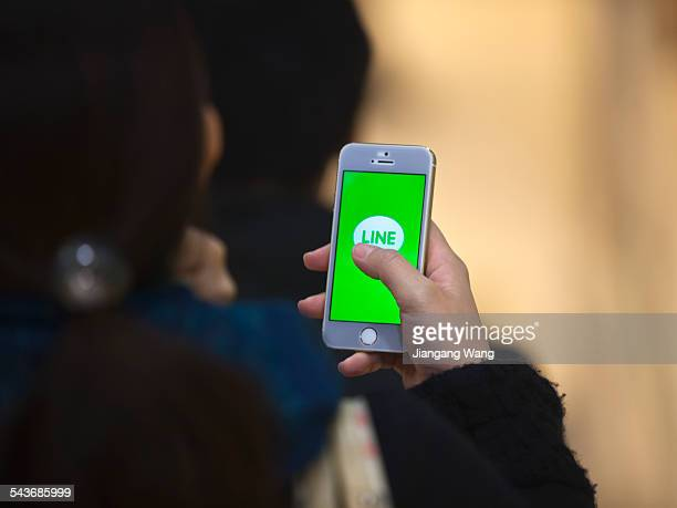 Yokohama Kanagawa Prefecture Japan March 9 2015 A woman is starting up the most popular communication application of Japan for her mobile phone in...