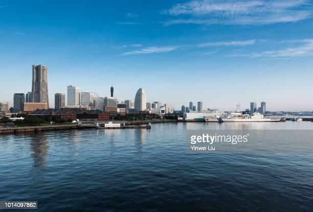 Yokohama Landmark Tower By Ooka River Against Clear Sky In City