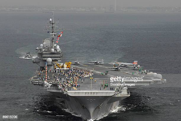 yokosuka, japan, september 17, 2006 - japanese guests and family members gather on the flight deck of uss kitty hawk (cv-63) to watch sailors prepare for a flight demonstration during a family day cruise.   - 航空母艦 ストックフォトと画像
