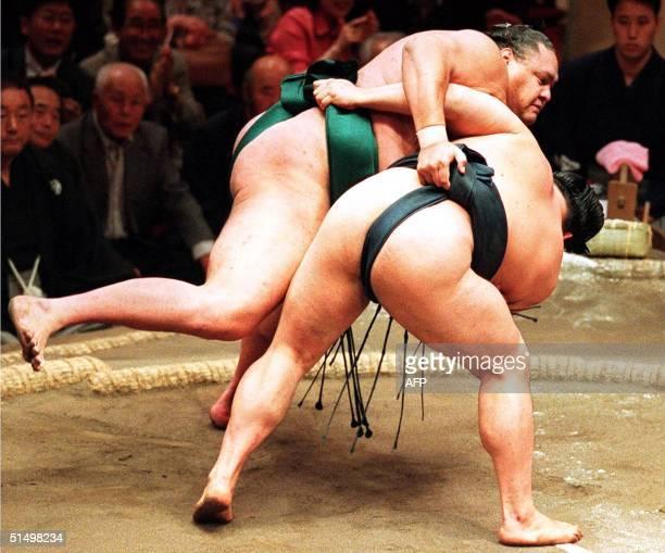 Yokozuna grand champion of Sumo Akebono is thrown by Yokozuna Takanohana to finish the summer sumo tournament by 132 in Tokyo 21 May 2000 Akebono's...