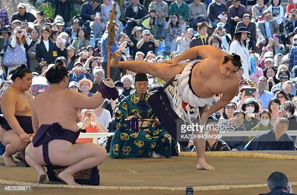 "Yokozuna Kakuryu of Mongolia offers a ritual entrance into the sumo wrestling ring during a ""honozumo,"" a ceremonial sumo exhibition at Yasukuni..."