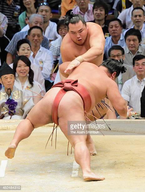 Yokozuna Kakuryu throws Yoshikaze to win during day eight of the Grand Sumo Nagoya Tournament at Aichi Prefecture Gymnasium on July 20 2014 in Nagoya...