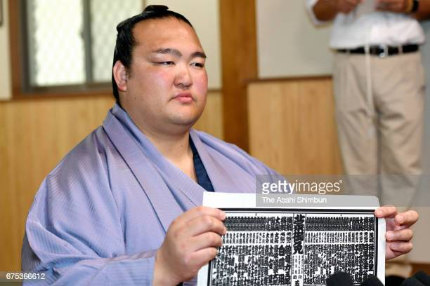 Yokozuna Kisenosato poses for photographs during a press conference as the new sumo ranking announced ahead of the Grand Sumo Summer Tournament at...