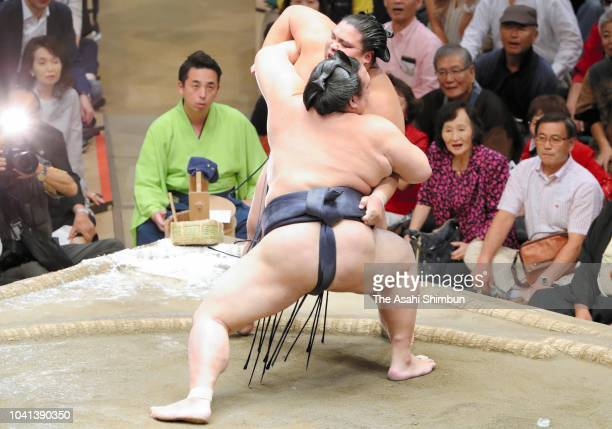 Shohozan pushes Mongolian wreslter Takanoiwa out of the ring to win on day twelve of the Grand Sumo Autumn Tournament at Ryogoku Kokugikan on...
