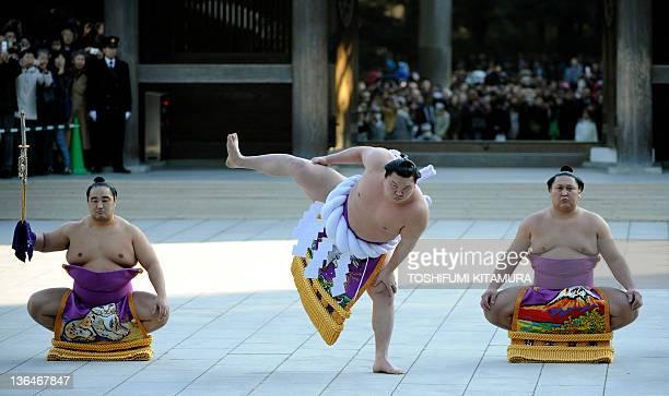 Yokozuna or grand champion of sumo Hakuho performs the ceremonial entrance into the ring among Tachimochi or swordbearer Aminishiki and Tsuyuharai or...
