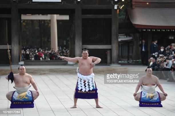 Yokozuna or sumo grand champion Hakuho of Mongolia accompanied by tachimochi or swordbearer Takarafuji and tsuyuharai or outrider Chiyoshoma takes...
