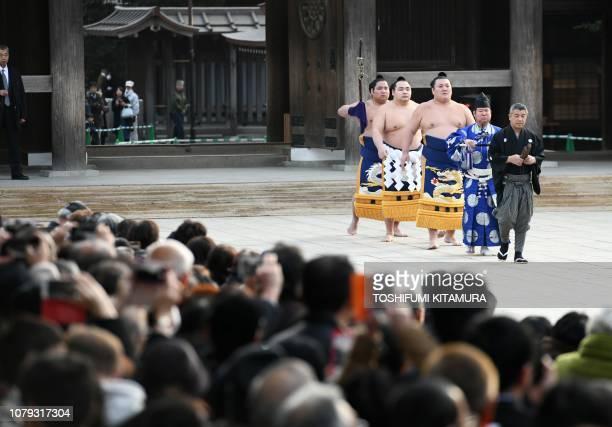 Yokozuna or sumo grand champion Kakuryu of Mongolia walks with tachimochi or swordbearer Nishikigi and tsuyuharai or outrider Ikioi as they enter the...