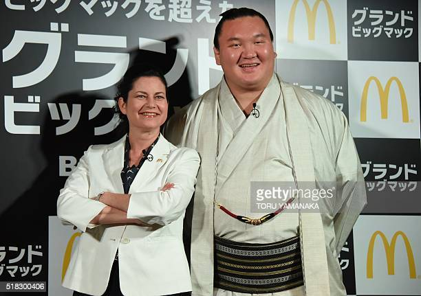 Yokozunaranked or grand champion sumo wrestler Hakuho poses with the president of McDonald's Japan Sarah Casanova for photographers during a...