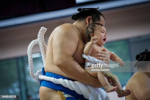 Yokuzuna wrestler hols a baby during 'Honozumo' ceremonial on April 16, 2018 in Tokyo, Japan. This annual offering of a Sumo Tournament to the divine...