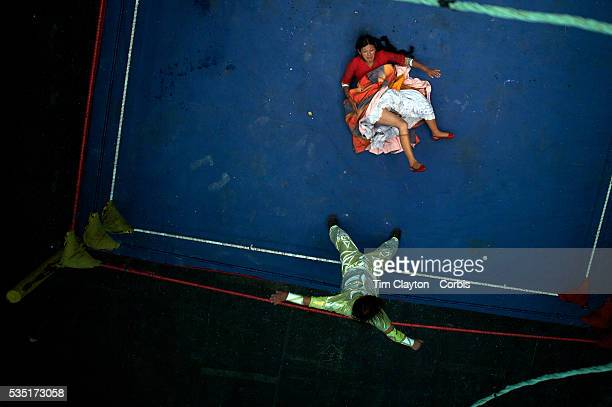 Yolanda La Amorosa lies on the canvas while fighting her male counterpart during the 'Titans of the Ring' wrestling group's Sunday performance at El...