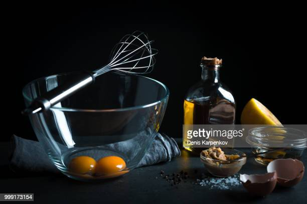 Yolks in a glass bowl, whisk for whipping, olive oil