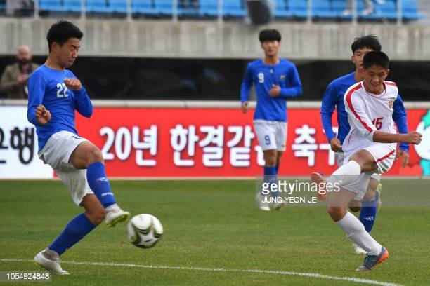 Yom Chol Gyong of the April 25 Sports Club of North Korea kicks the ball past a footballer from the Gangwon-do team of South Korea during their match...