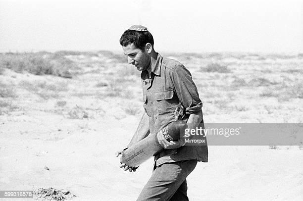 Yom Kippur War The Fourth Arab Israeli War October 6th to 25th 1973 Israeli Soldier wearing Skullcap carries artillery shell for tank Sinai Desert...