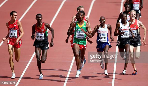 Yomif Kejelcha of Ethiopia and Mohamed Farah of Great Britain cross the finish line in the Men's 5000 metres heats during day five of the 15th IAAF...