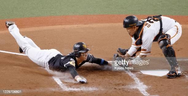 Yomiuri Giants catcher Takumi Oshiro tags out SoftBank Hawks runner Ryoya Kurihara in the fourth inning in Game 1 of the Japan Series at Kyocera Dome...