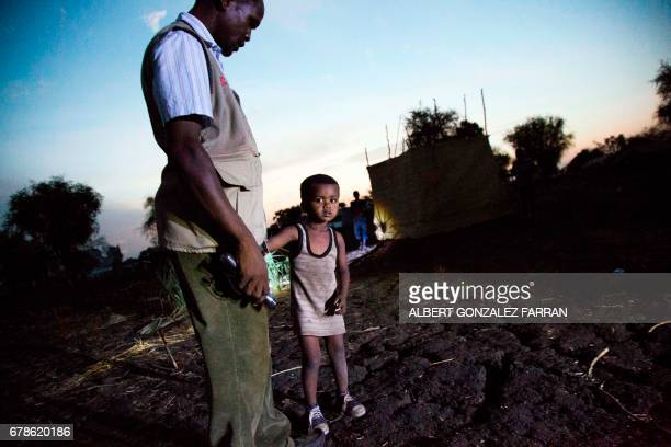 TOPSHOT Yonan Samani a Sudanese refugee and team leader of the Community Night Watchers in Doro refugee camp finds and talks with a lost child on May...