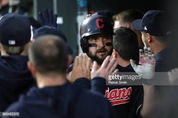 Yonder Alonso of the Cleveland Indians celebrates in the dugout with teammates after hitting a a tworun home run during the second inning against the...