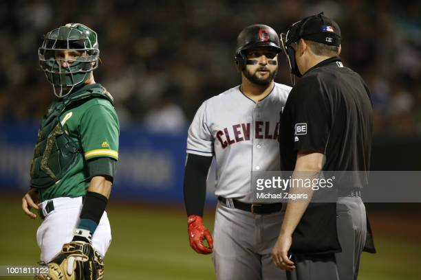 Yonder Alonso of the Cleveland Indians has words with Umpire Lance Barrett during the game against the Oakland Athletics at the Oakland Alameda...