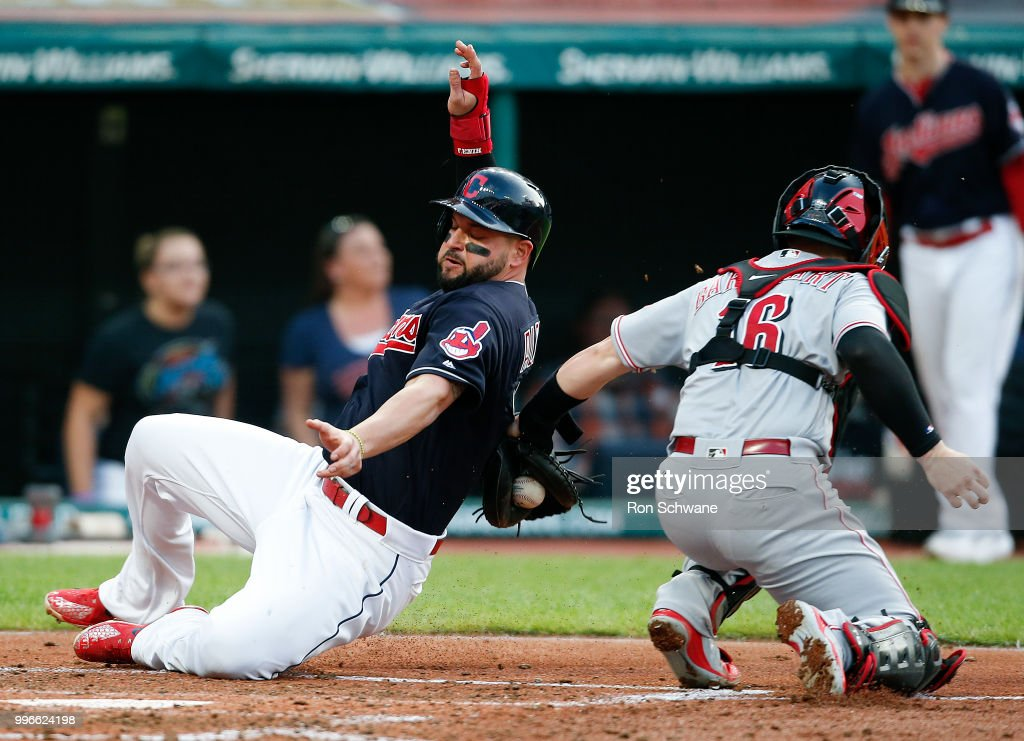 Yonder Alonso #17 of the Cleveland Indians scores past Tucker Barnhart #16 of the Cincinnati Reds on a single by Yan Gomes #7 during the third inning at Progressive Field on July 11, 2018 in Cleveland, Ohio.