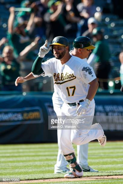 Yonder Alonso of the Oakland Athletics is congratulated by third base coach Steve Scarsone after hitting a walk off home run against the Minnesota...