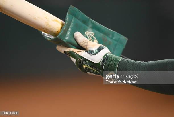 Yonder Alonso of the Oakland Athletics puts pinetar on his bat in the ondeck circle against the Los Angeles Angels of Anaheim in the bottom of the...