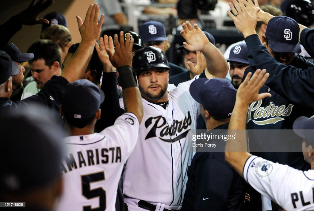 Yonder Alonso #23 of the San Diego Padres is welcomed into the dugout after scoring during the eighth inning of a baseball game against the St. Louis Cardinals at Petco Park on September 10, 2012 in San Diego, California. The Padres won 11-3.