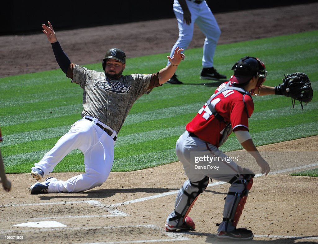 Yonder Alonso #23 of the San Diego Padres scores ahead of the tag of Kurt Suzuki #24 of the Washington Nationals during the fifth inning of a baseball game at Petco Park on May 19, 2013 in San Diego, California.