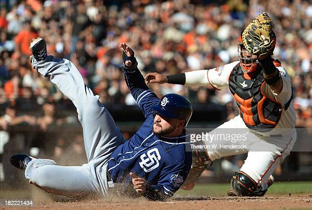Yonder Alonso of the San Diego Padres scores, sliding past the tag of Hector Sanchez of the San Francisco Giants during the ninth inning at AT&T Park...