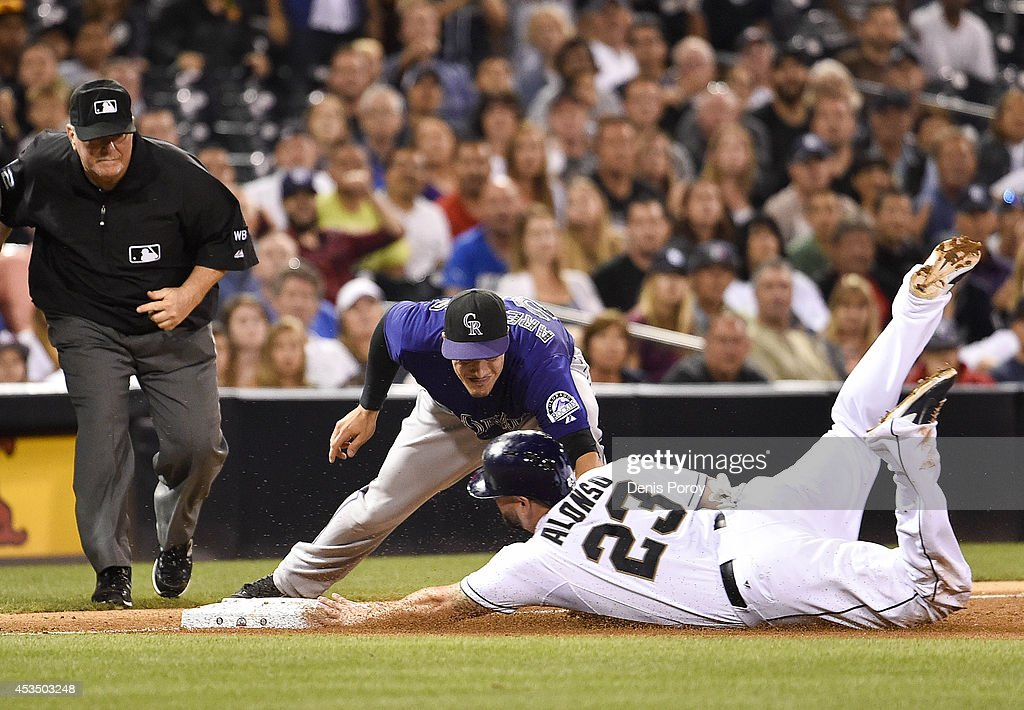 Yonder Alonso #23 of the San Diego Padres slides into third base ahead of the tag of Nolan Arenado #28 of the Colorado Rockies as umpire Dana DeMuth makes the call during the sixth inning of a baseball game at Petco Park August, 11, 2014 in San Diego, California.