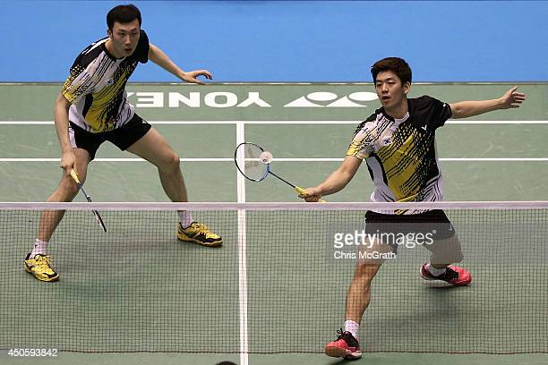 Yong Dae Lee of Korea returns a shot as team mate Yeon Seong Yoo watches on during their Men's Doubles semi final match against Angga Pratama and...