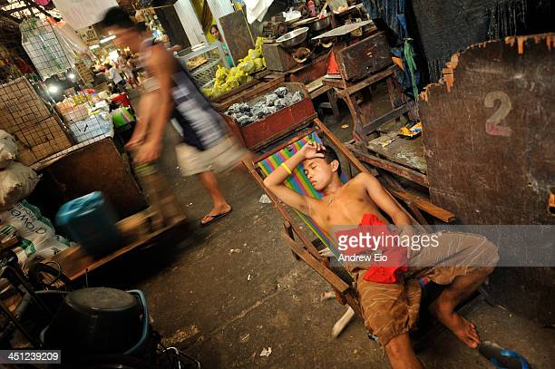Yong man catches a quick nap on a deckchair in the centre of the food market at Quiapo Market in Manila. In the background the other workers pass by...