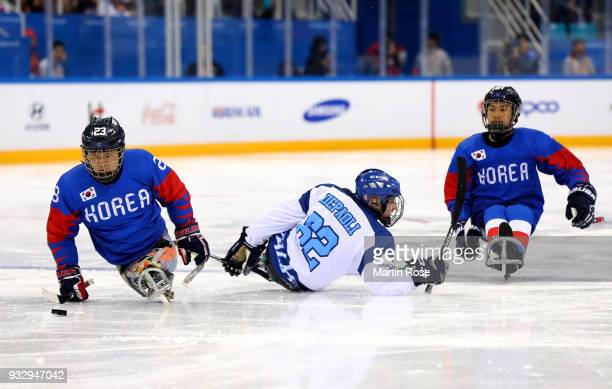 Yong Min Lee of Korea battles for the puck with Christoph Depaoli of Italy in the Ice Hockey bronze medal game between Korea and Italy during day...