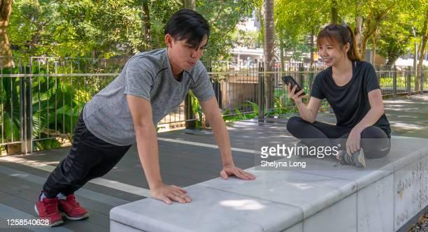ヨンスポーツウーマンは、男性のアルトレットの腕立て伏せの数を計算します - extra long ストックフォトと画像