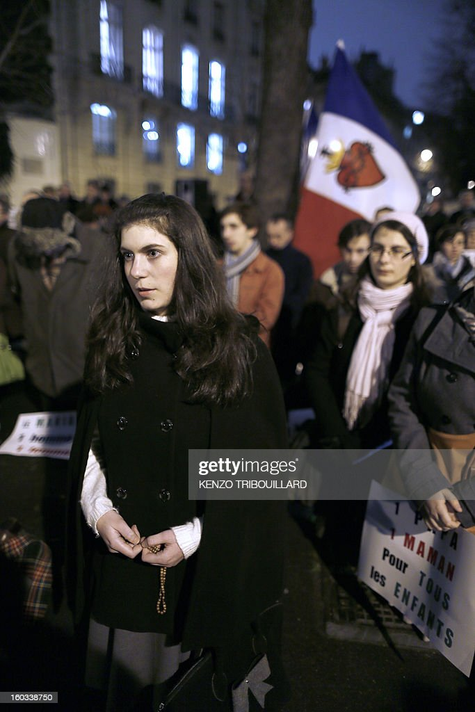 A yong woman prays with a rosary during a protest organized by fundamentalist Christians group Civitas Institute against same-sex marriage on January 29, 2013 in Paris. France's parliament began today examining draft legislation on same-sex marriage after months of rancorous debate and huge street protests by both supporters and opponents. Background, a French national flag with a sacred heart.