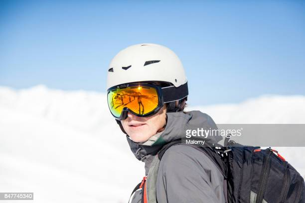 Yong woman with ski helmet, ski goggles and backpack in front of blue sky and snow capped mountains.