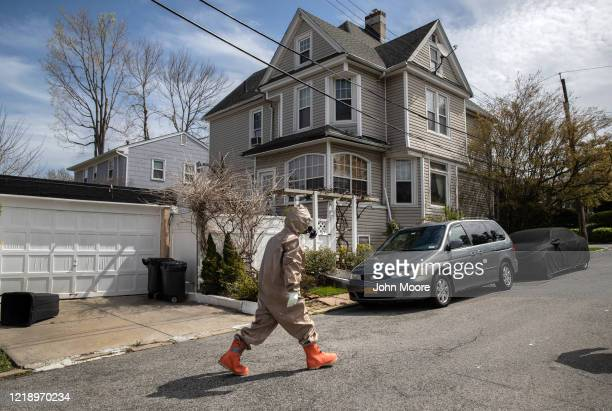 A Yonkers Fire Department EMT clothed in full personal protective equipment walks back to his truck after helping carry a patient with COVID19...