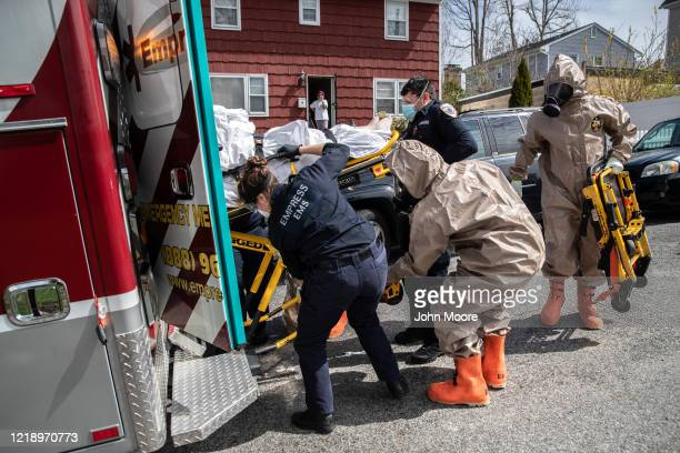 Yonkers Fire Department EMTs clothed in full personal protective equipment assist Empress EMS EMTs to transport a patient with COVID19 symptoms to a...