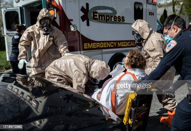 Yonkers Fire Department EMTs clothed in personal protective equipment assist an Empress EMS medic to transport a patient with COVID19 symptoms to a...