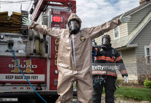 Yonkers Fire Department EMTs decontaminate their full personal protective equipment after helping carry a patient with COVID19 symptoms out of her...