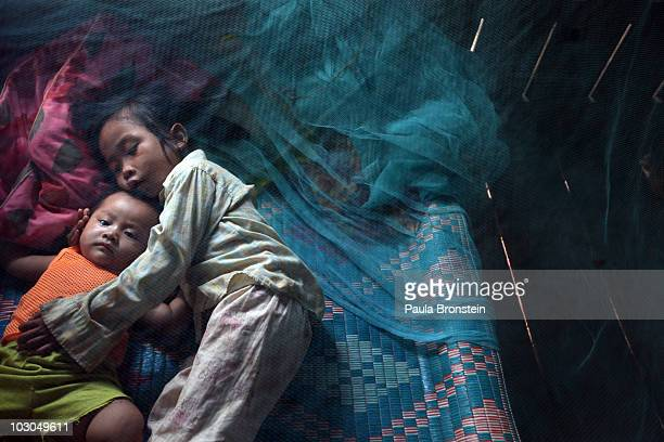 Yonta rests with her sister Montra and brother Leakhena 4months under a mosquito bed net keeping dry from the monsoon rain July 18 2010 in Prey Mong...