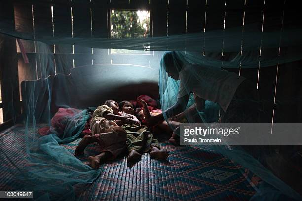 Yonta rests with her sister Montra and brother Leakhena, 4months under a mosquito bed net keeping dry from the monsoon rain July 18, 2010 in Prey...