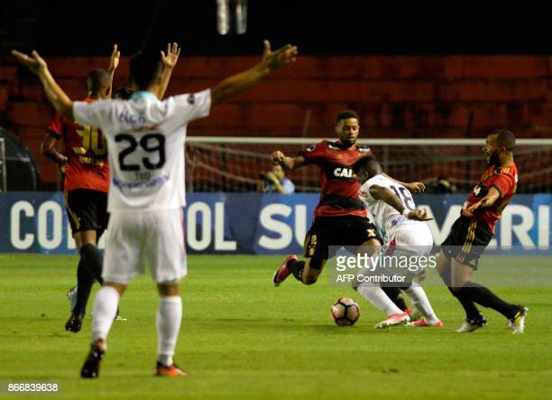 Yony Gonzalez of Colombia's Junior de Barranquilla vies for the ball with Andre and Samuel Xavier of Brazil's Sport Recife during their Sudamericana...